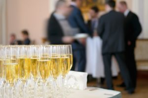 Champagne for participants of the presentation. Champagne glasses against the background of business people.